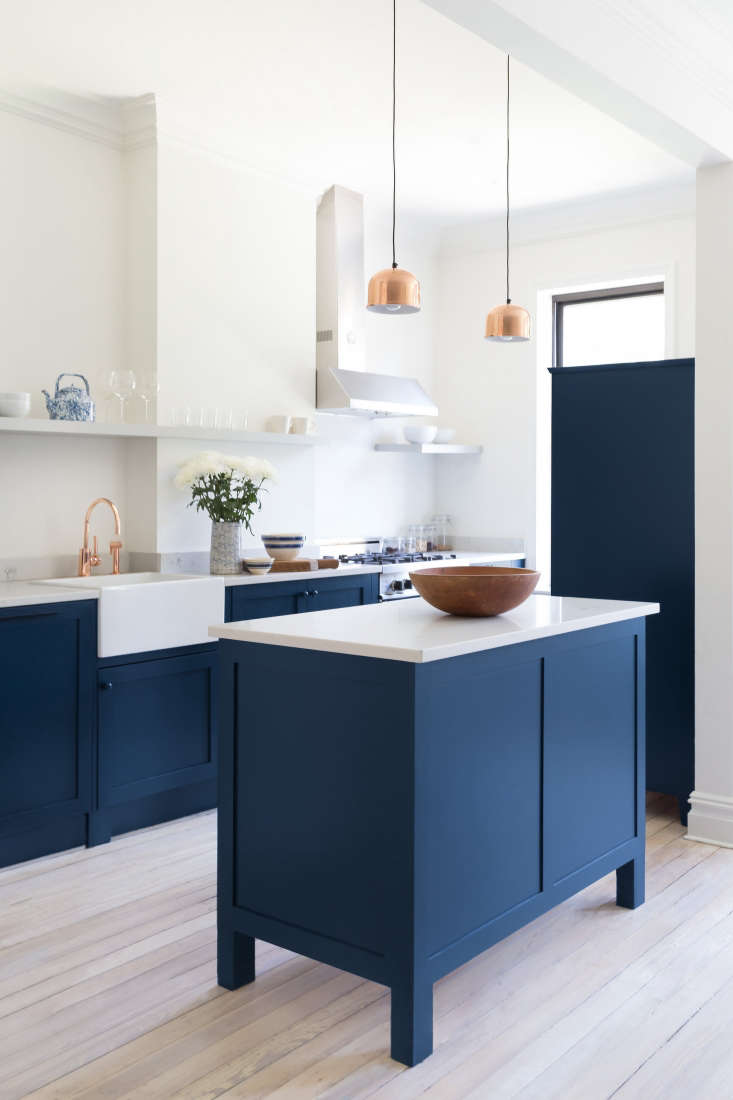The kitchen is defined by its blue-and-white motif and Scandinavian-looking floors (the existing subfloors, bleached). Photograph by White Arrow from Before and After: A Buzzfeed Founder's Renovated Rowhouse, Budget Edition.