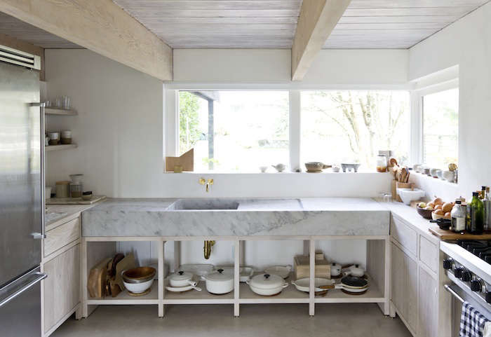 open shelving beneath a marble countertop, and in a niche, keeps cookware on di 10