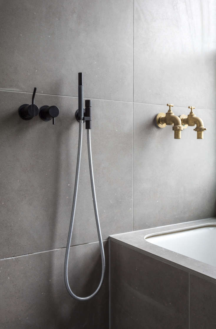 Refined meets rustic: the matte black Shower Mixers are from Vola and thebrass bath taps are another score from a hardware store in Braga, Portugal: &#8