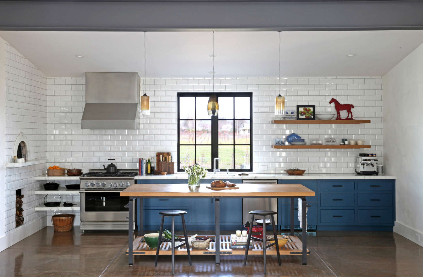 Built-in shelves, rather than cabinets, accommodate a generous range in In California Wine Country, A Modern Farmhouse for a Brit and a Texan.
