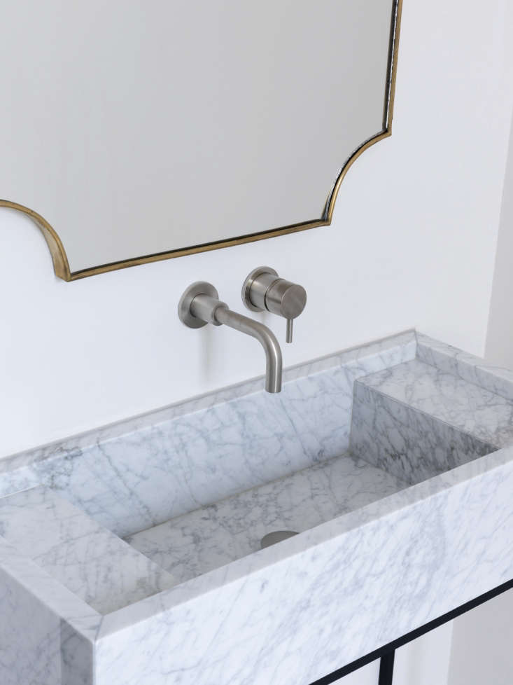 Maclean incorporated ledges into the Carrara marble basin designed just for the house. The stainless faucet is theM Pro Single-Lever Wall Mount Lavatory Faucet from Crosswater of London.