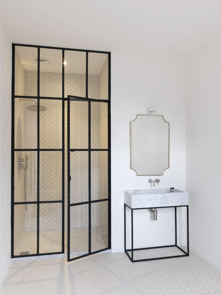 The herringbone-tiled shower is fronted by custom steel-frame doors with divided glass panels fabricated by one of Maclean&#8