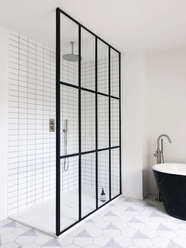 A steel-frame window wall divides the open shower from the black-and-white tub (Maclean foundit on eBay and doesn&#8