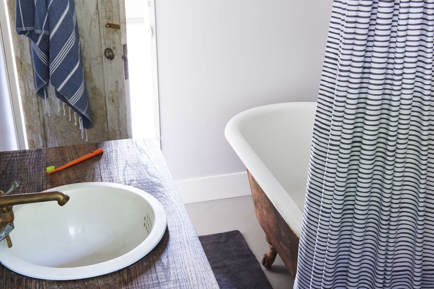 The small bath is well-appointed for country life, with an antique cast-iron tub andvintage porcelain sink.