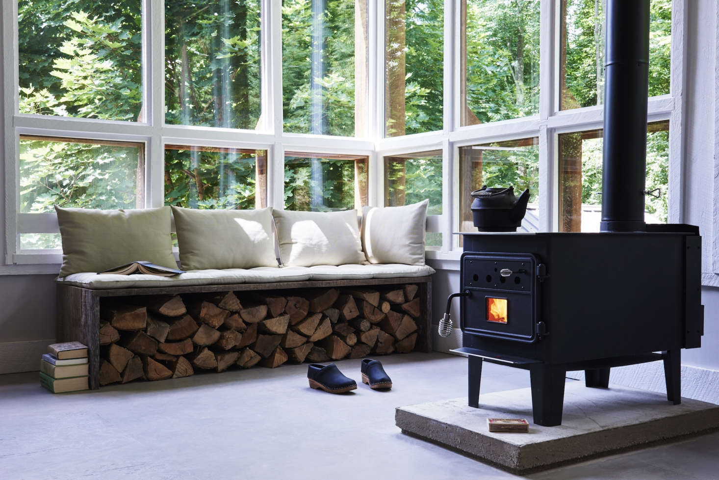 Near the Vogelzang Durango woodstove is an inventive storage solution: stacked logstucked beneath a bench.