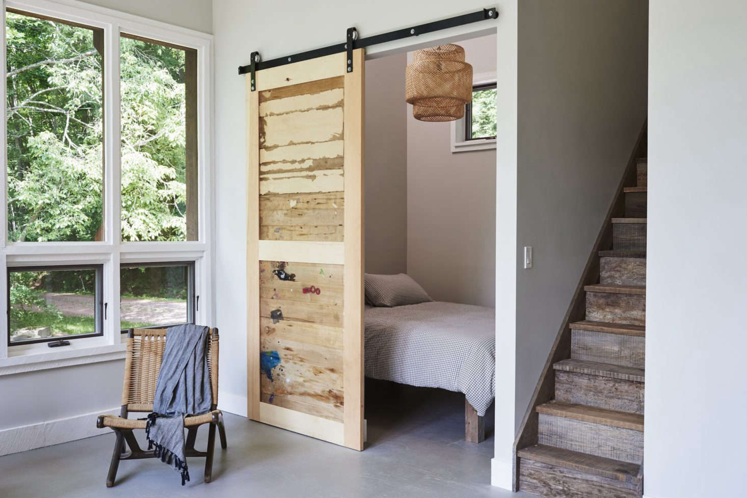 A sliding barn door is made of salvaged wood from the artist&#8