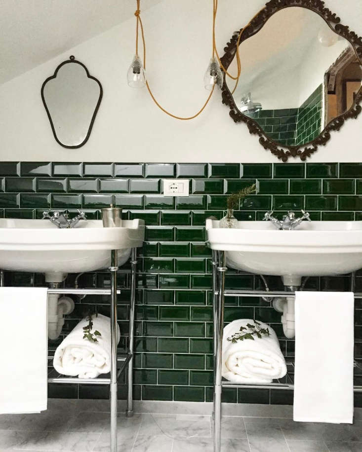 The guest baths are tiled in glossy deep green.In room No. : marble floors, crystal pendant lights from Ebb & Flow, and antique mirrors above twin washbasins.