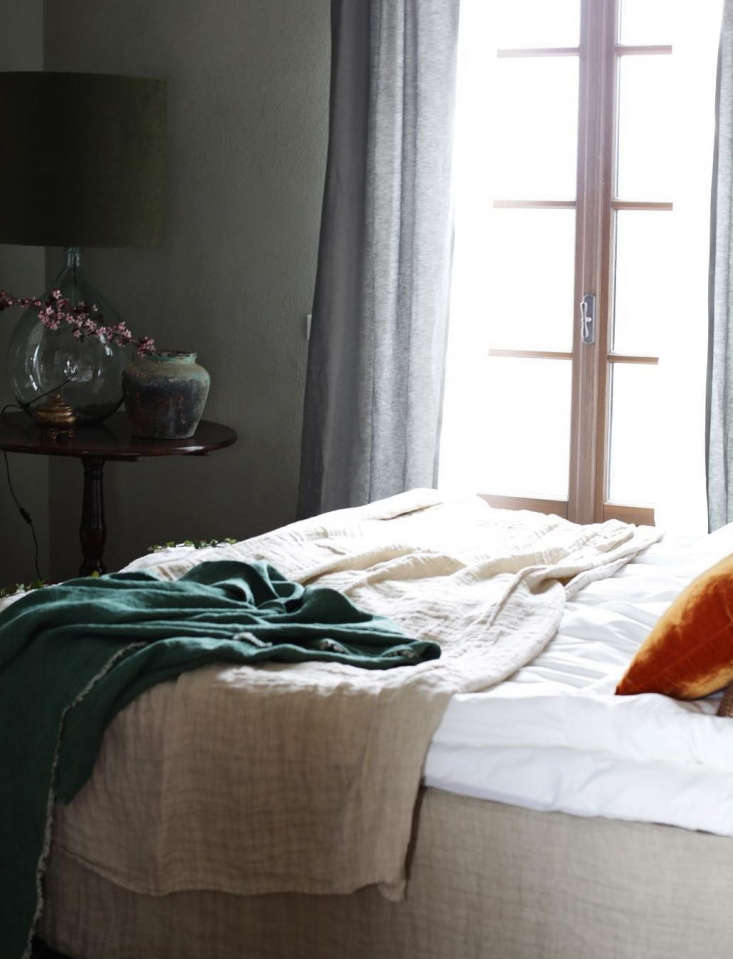 Countryside-chic: linens draped casually on a bed. The throws are from Maison de Vacances.