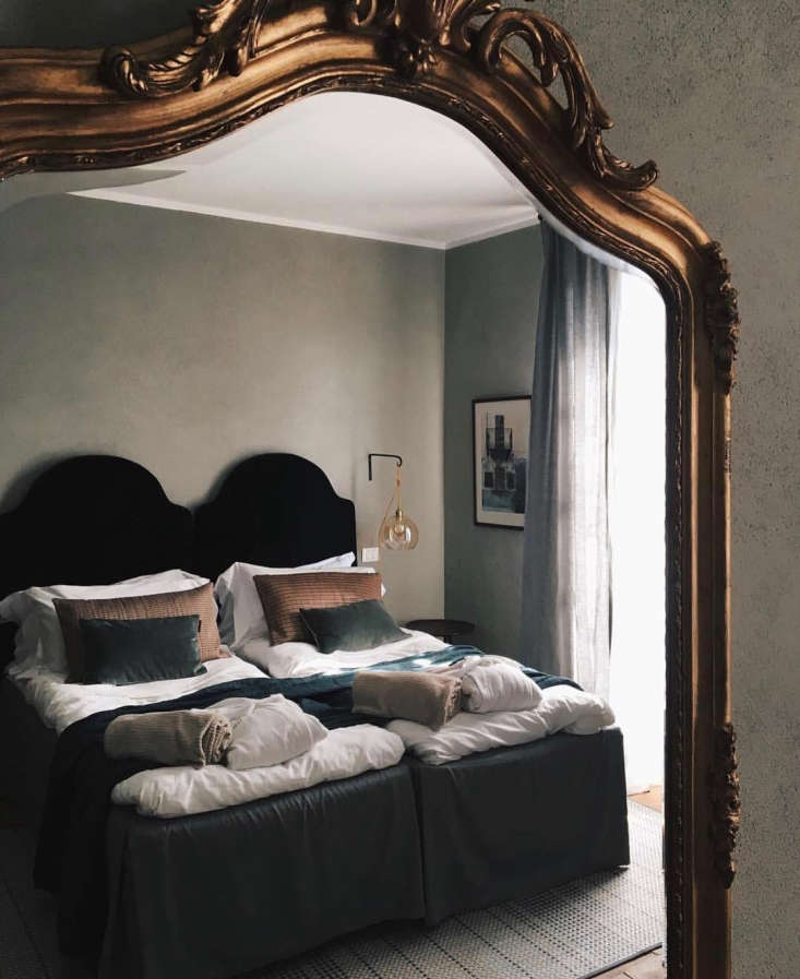 The makings of a Villa La Madonna guest room: custom rugs and cushions by Bolon, dramaticvelvet headboards, dusty-green- and rust-coloredthrows, and ochre-hued glass pendant lights.