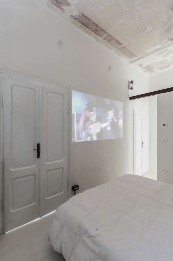 white bedroom with projector television italy archiplan studio