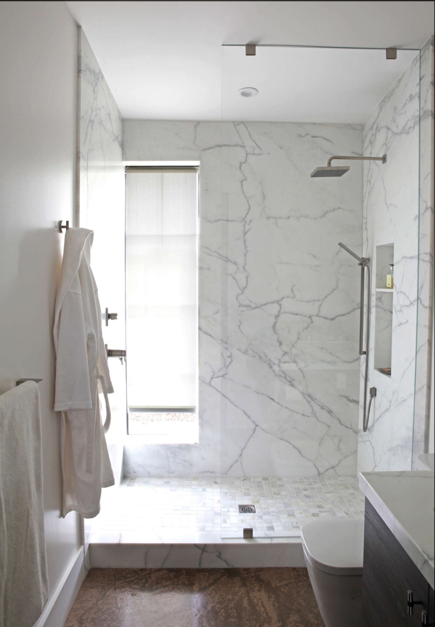 In the same Sonoma house, a narrow, water-resistant roller shade is tucked into a window recess in the marble shower. Photograph by Karen Steffens for Remodelista.