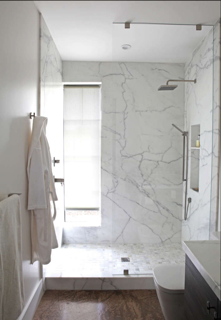 In the same Sonoma house, anarrow, water-resistant roller shade is tucked into a window recess in the marble shower. Photograph by Karen Steffens for Remodelista.
