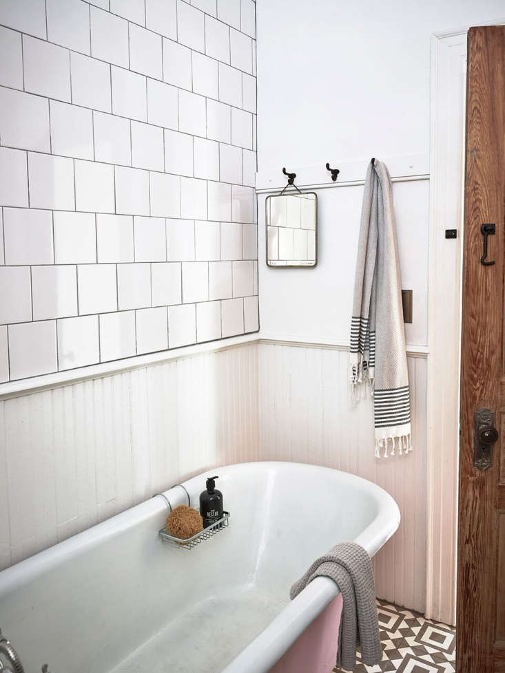 Anthony added a beadboard surround in the bath. The floor tile from Cle, and the original clawfoot tub is painted pink.