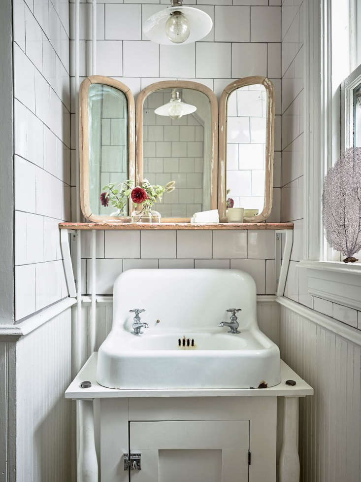 The bathroom has a custom wood vanity and vintage cast iron sink. The light is custom with a Schoolhouse Electric Shade.