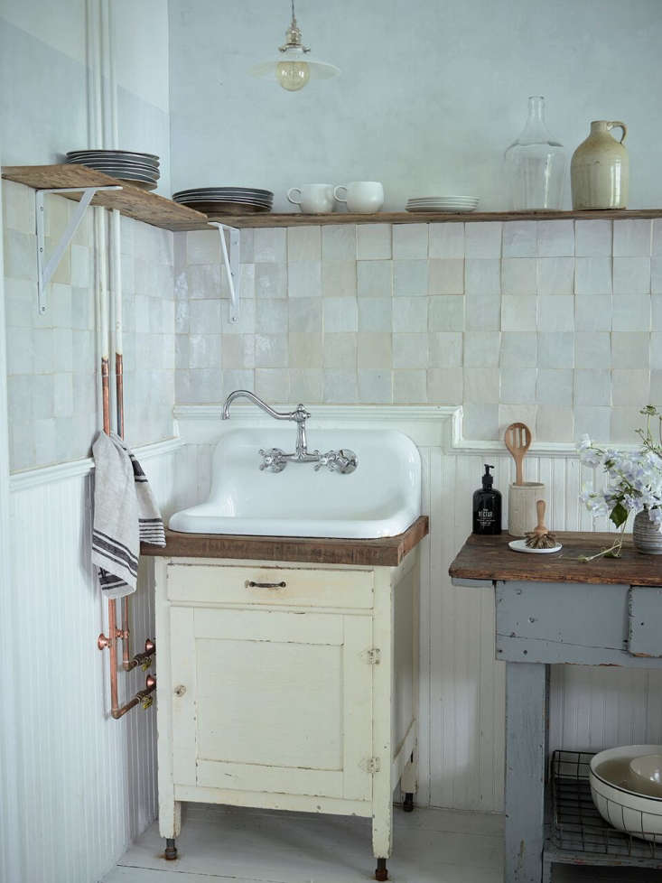 The sink console is vintage and the Polished Chrome Vintage Wall-Mounted Centerset Faucet with Metal Cross Handles is from Kingston Brass; $loading=
