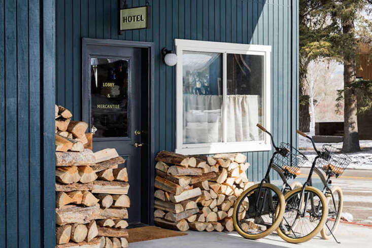 Go West A Mountain Lodge in Jackson WY by a Brooklyn Design Studio The Anvil Hotel entrance is surrounded by firewood used throughout the year. The building is painted in Benjamin Moore&#8\2\17;s Regent Green. Bikes are available for guests for rent.