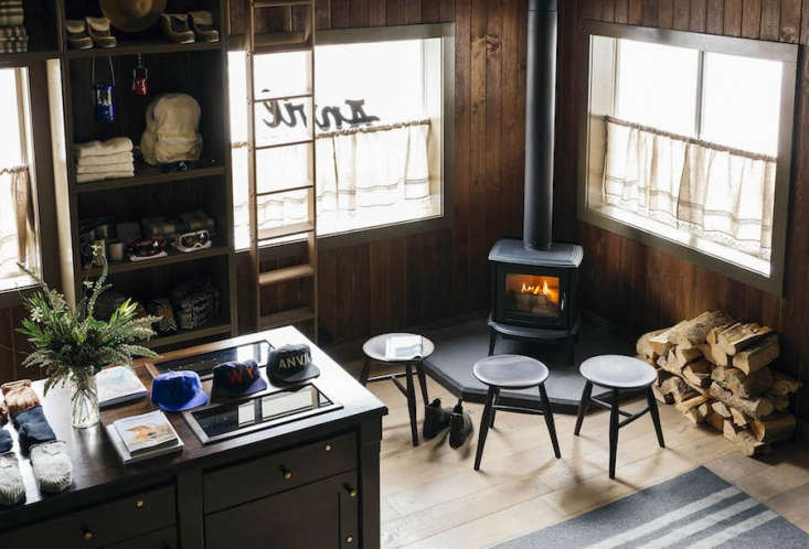 Go West A Mountain Lodge in Jackson WY by a Brooklyn Design Studio Gathering encouraged: In thewood paneled lobby, simple stools surround a freestanding woodstove.