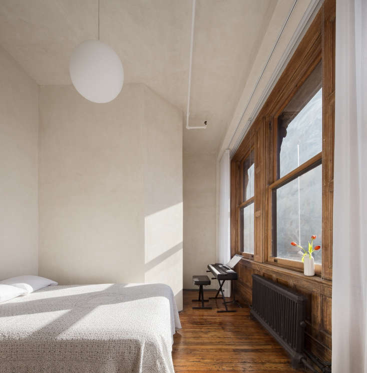 bedroom in loft worn wood floors globe pendant