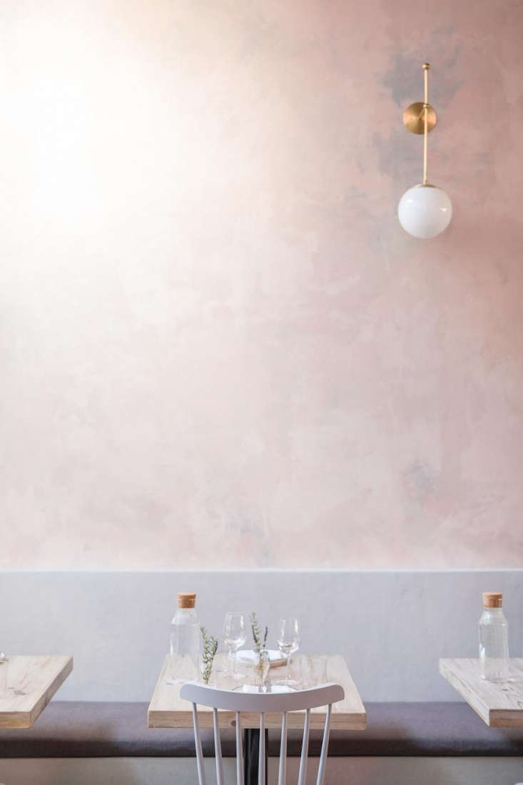 A subtly-pink wall and pastel-painted chairs. On each table: a cork-top glass water bottle and fresh herbs.