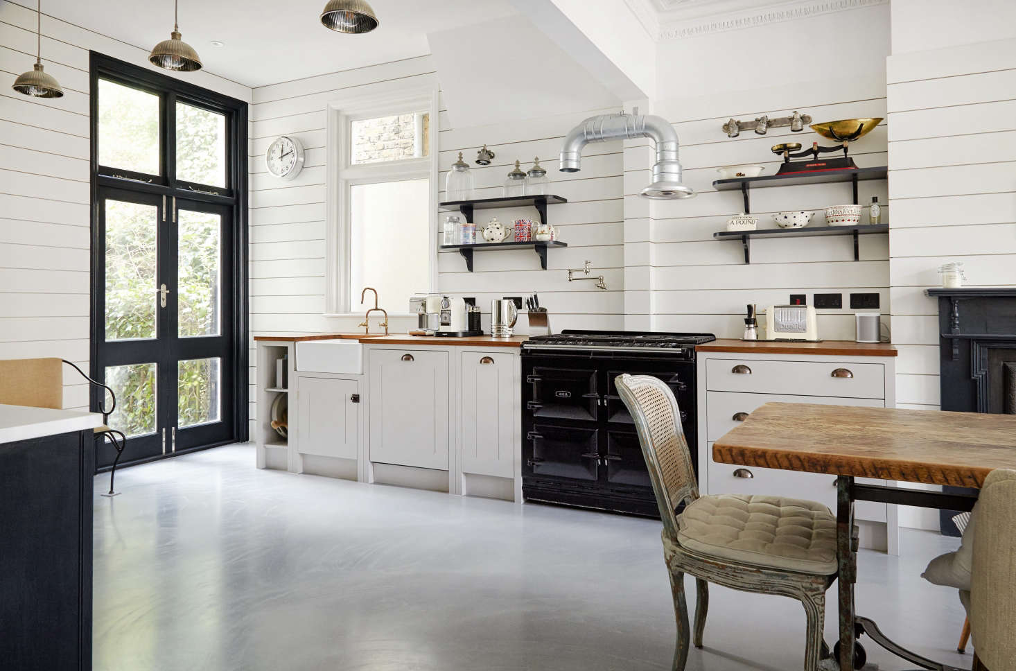 Glass-paneled double doors (which lead out to the yard)and the use of shelves in lieu of overhead cabinets keep the space feeling open and airy.