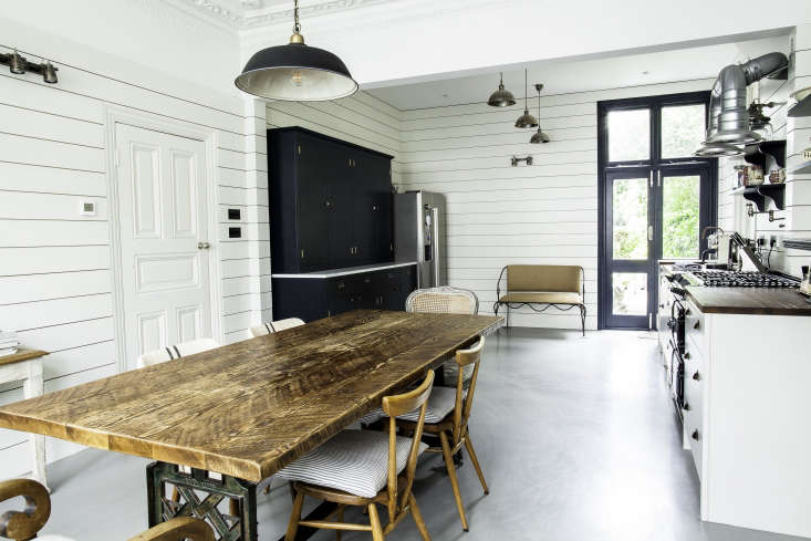 A large side-by-side fridge and freezer stands in the corner next to a British Standard tall wooden cabinetpainted Farrow & Ball Railings. Seating options at the dining table include apair of Ercol Stacking Chairs.