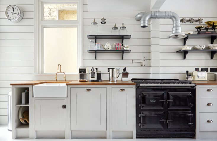 The British Standard setup includes(from left) an open tray space, a single under-sink cabinet, an integrated dishwasher door, a drop-down bin, and a trio of pan drawers. They&#8