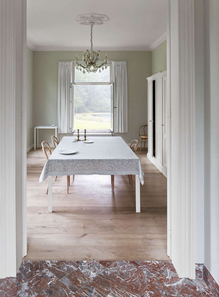 A bare dining room floor reflects summery light from a generous window in theth-century manse of Belgian architectsBram Seghers and Inge Buyse. Photography by Frederik Vercruyssevia This Is Paper.