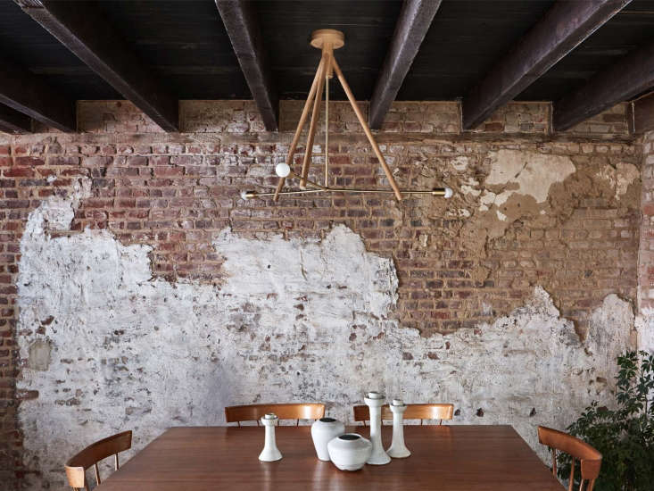 TheLodge Chandelier Three in natural oak and hewn brass hangs above a dining table.