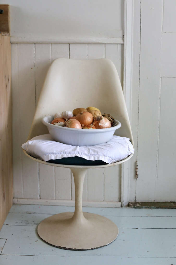 A vintage Saarinen Tulip chair holds a bowl of onions in the kitchen.