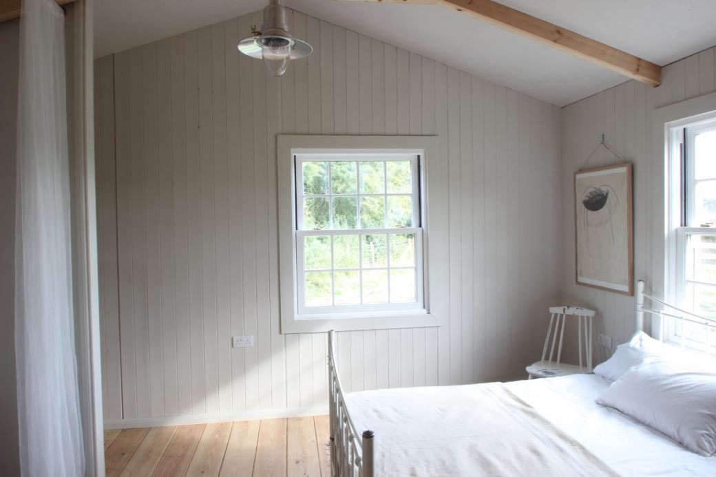 In this simple cottage bedroom, craftsman Edward Collinson employed TGV or V-groove cladding to emphasize the height of this cozy bedroom. Streamlined white furnishings further enhance the airy feel. See more at A Simple Bespoke Cabin in North Yorkshire, Father/Son Edition.