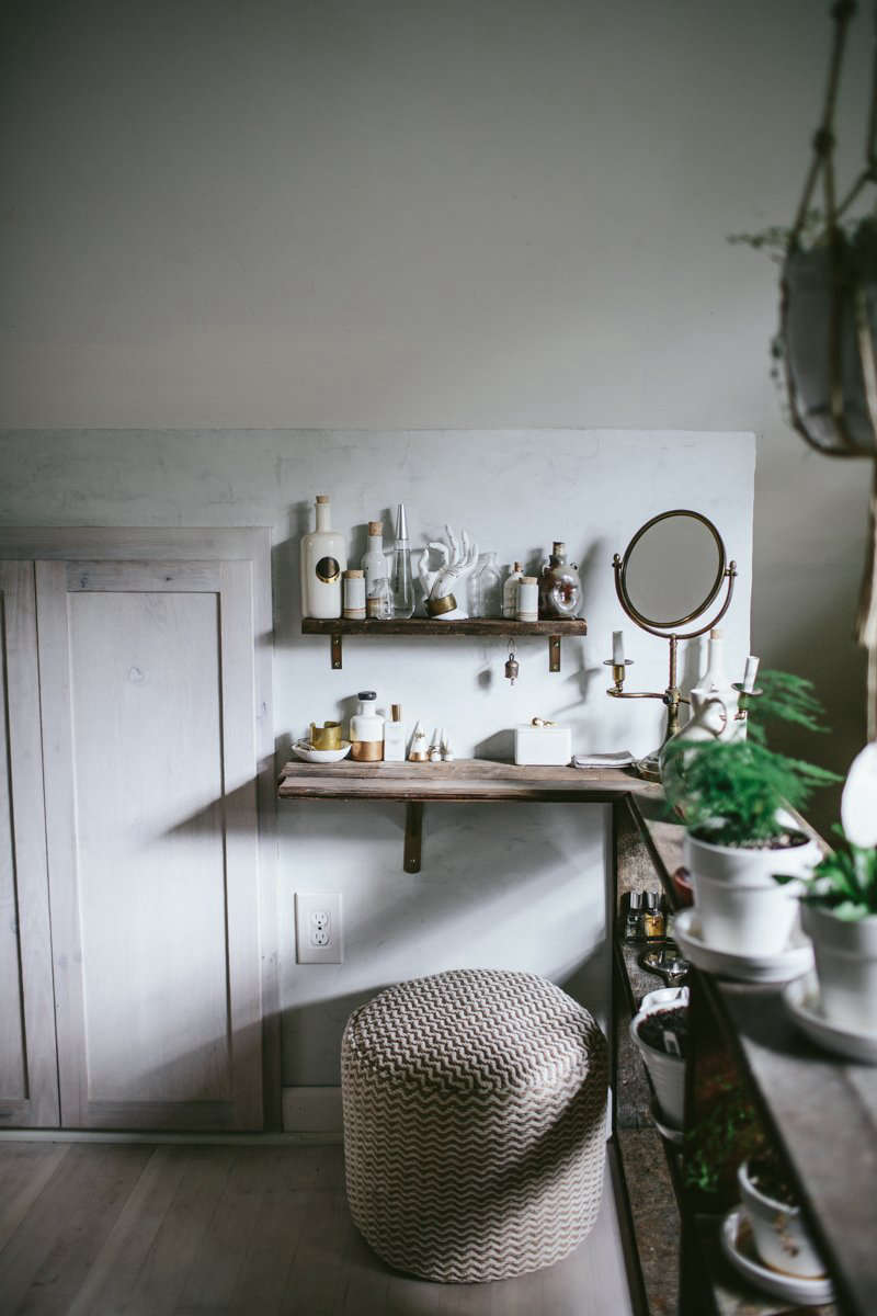 The shelving continues into a small, low-ceilinged area under the eaves, creating a built-in vanity.