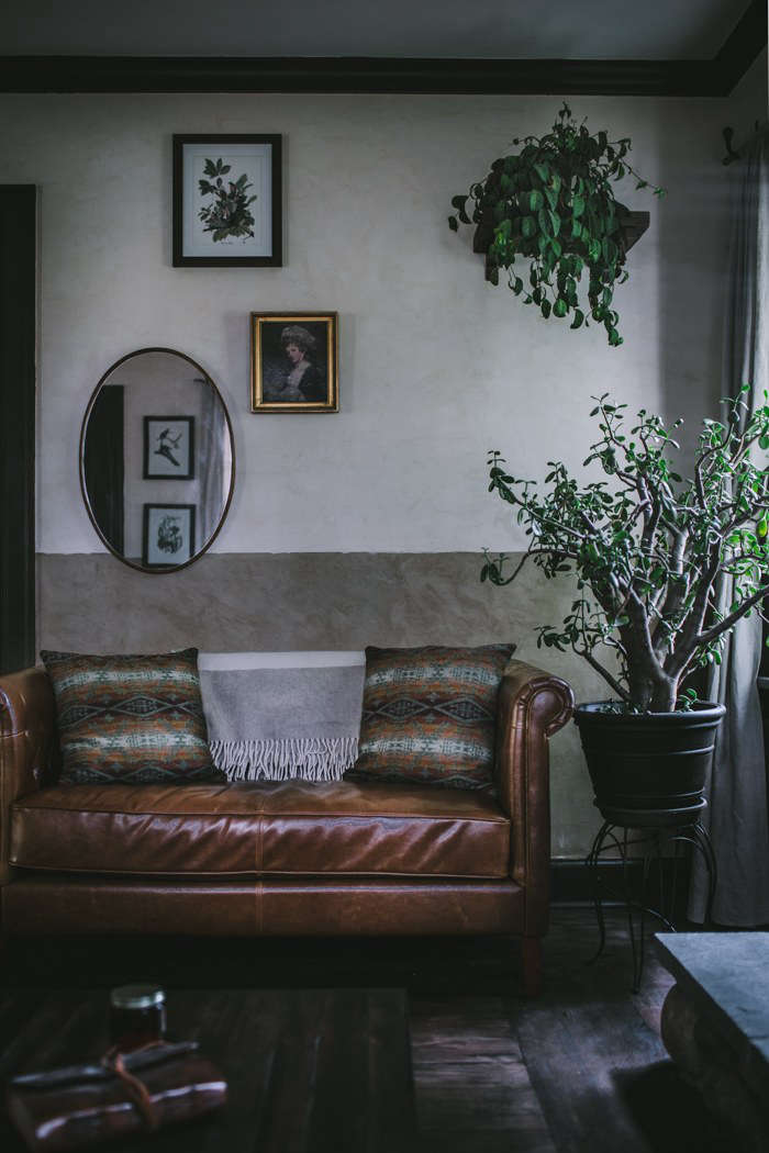 Houseplants and a mirror keep the room from feeling too dim.