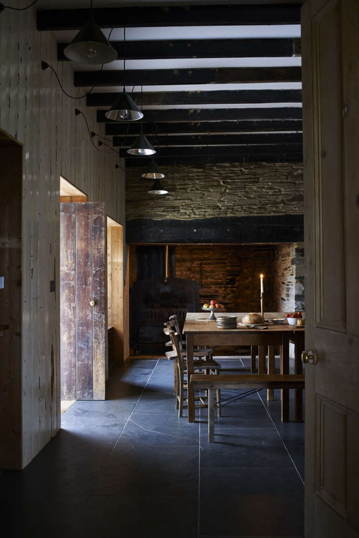Original doors illuminate the kitchen interior. The high ceilings feature salvaged beams from the original structure.