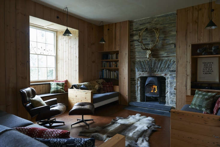 In the living area, the original slate walls and fireplace—quarried 0 years ago from the river gorge—peek out from the pine paneled walls.