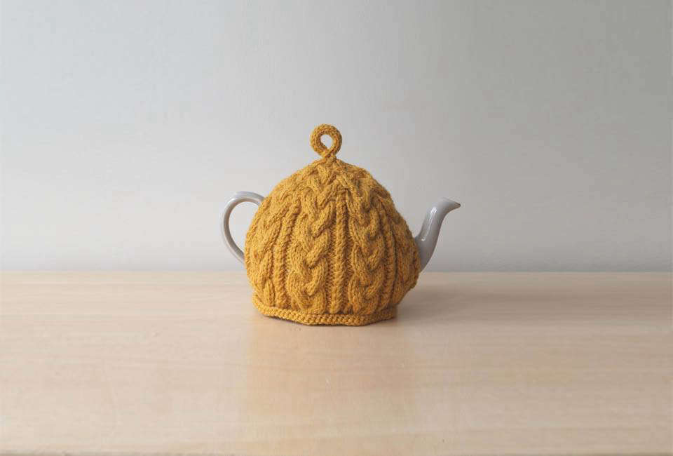 A Golden Yellow Knitted Tea Cosy is available from Lindy Knits, a seller on Etsy, for $.src=