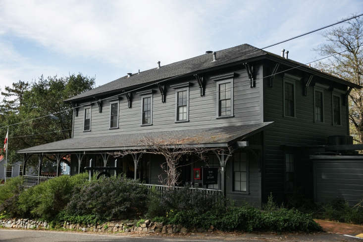 A Northern California Roadhouse Inn Restored with Whimsy and a Hint of Surrealism The building's exterior is painted in Benjamin Moore's Black Panther—in a flat finish with the trim in gloss to emphasize existing Italianate architectural details. (SeeDark Matter: \10 Design Ideas to Steal from Houses with Dramatic Facades on Gardenista for more ideas.)
