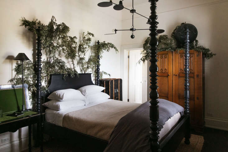 A Room at the Inn 6 Shops with Upstairs Accommodations A four poster bed is adornedwith foraged branches to create the feeling of sleeping in the woods.