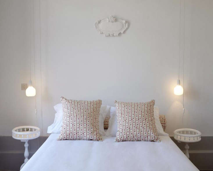 The bed is outfitted in crisp white linens with matching accent pillows and bolster.