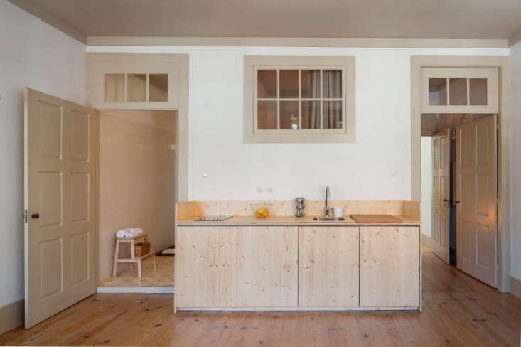A plywood kitchenette with hidden, under-counter appliances, an electric two-burner cooktop, and a sink in a renovated family house in Porto, Portugal.