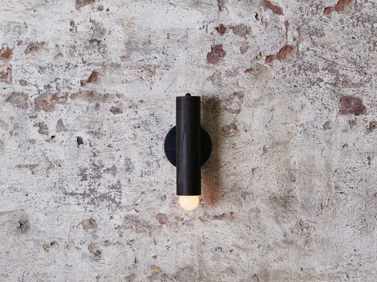 The sconce is availablein natural oak with a hewn brass backplate or in oxidized oak with ablackened brass backplate (shown here).