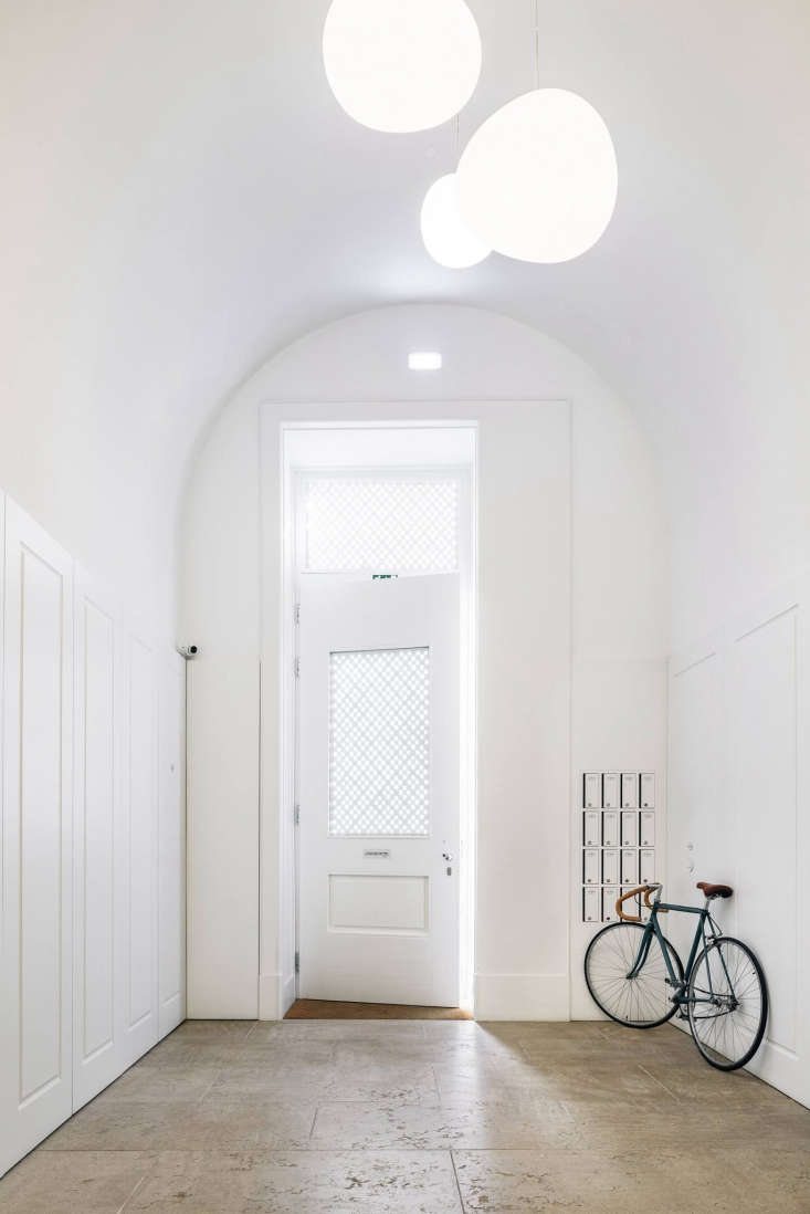 The all-white entryway, with a bicycle available for rent. The original detailing and soaring ceilings of the factory were preserved throughout.