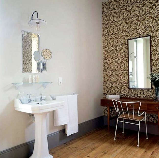 Select walls in the same guest room (complete with sink and dressing table) are covered with the custom Eley Kishimoto wallpaper; the Antelope chair is by Ernest Race.
