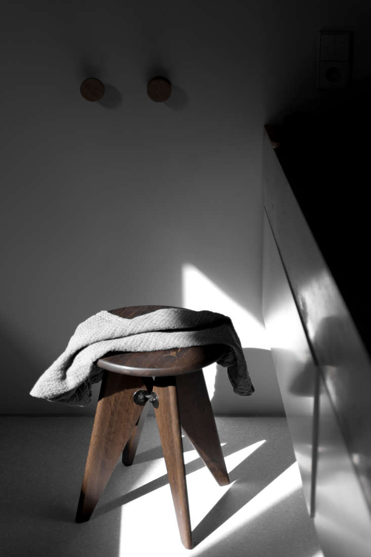A Jean Prouvé Tabouret Solvay Stool, still in production by Vitra,is perched between the sink and tub.