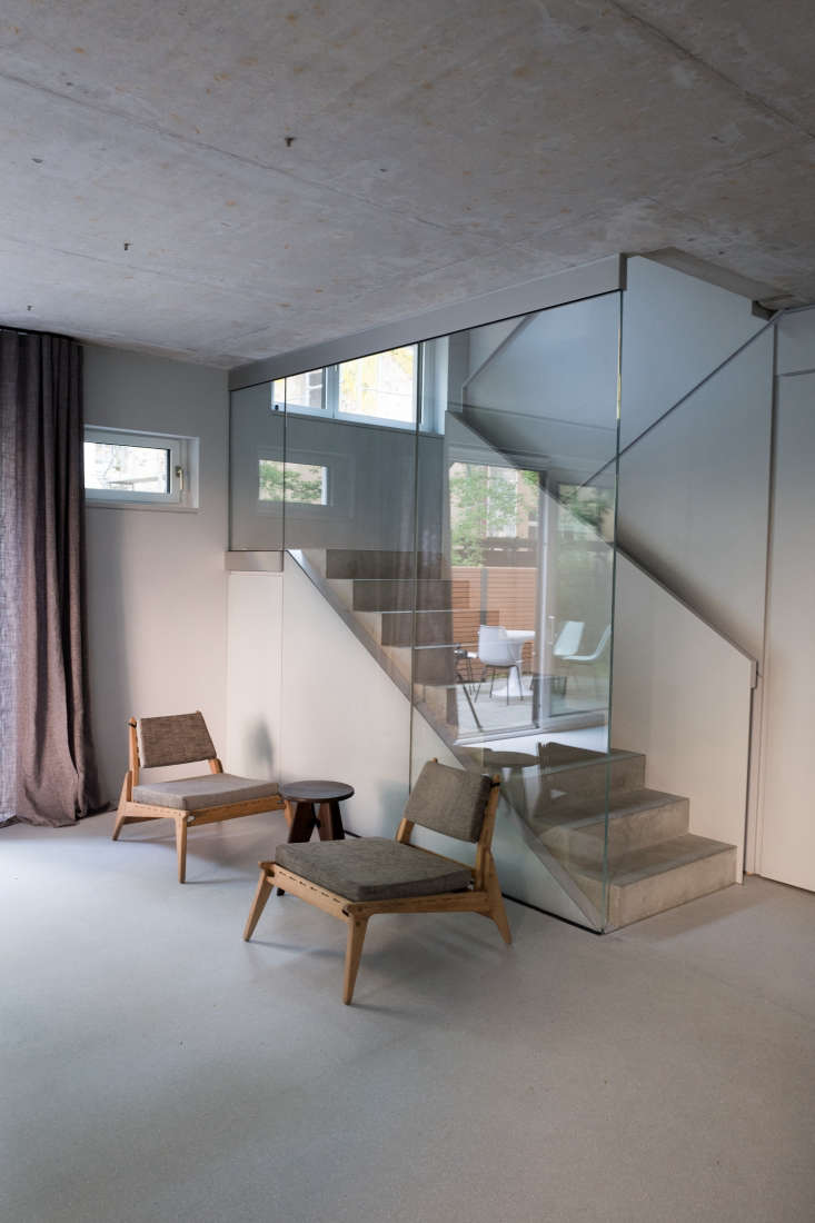 A glass-enclosed concrete stair is anarrestingelement introduced by DesignYouGo. It enables natural light to filter from skylights on the top floor all the way through the house.