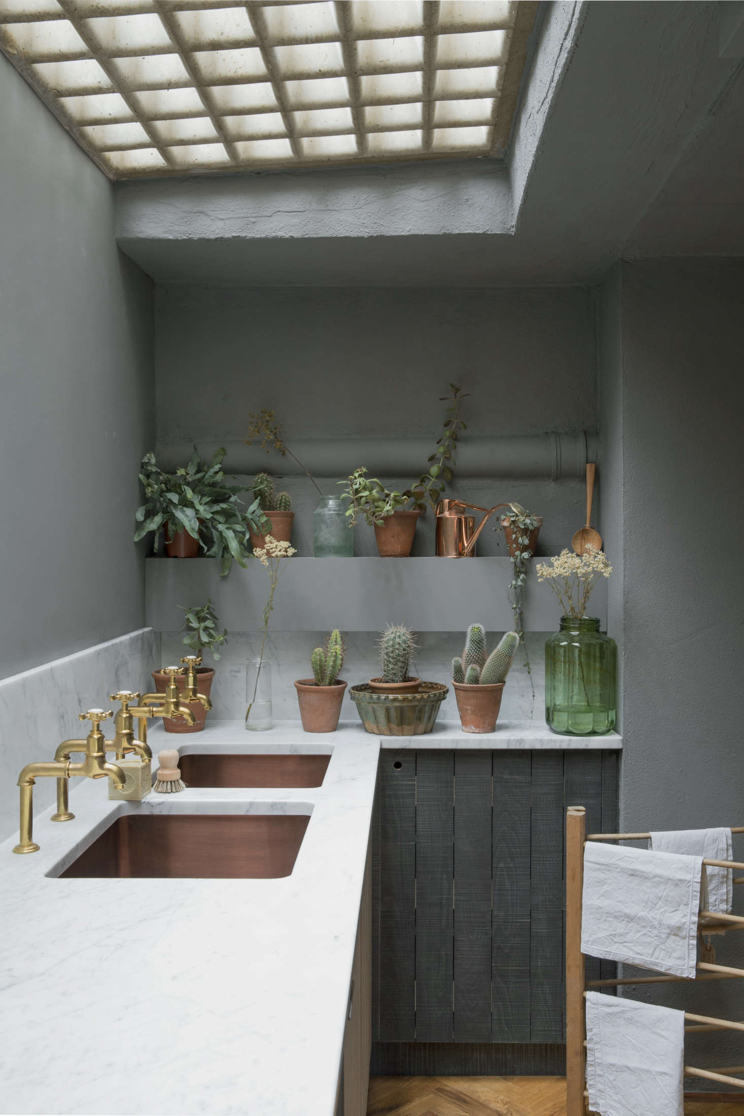 A lineup of succulents and other plants bring color to the space, and a gridded skylight filters in a soft, natural light. The walls are painted Mole&#8
