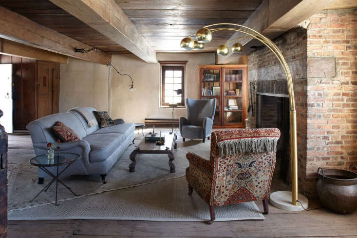The English Roll Arm Sofa is from Restoration Hardware and the brass arc lamp with Italian marble baseis from a Hudson antiques shop. The couple found the th century chair in Santa Barbara; the lamp mounted onthe beam is a vintage FariesFixturesdentists lamp from Luddite Antiques.