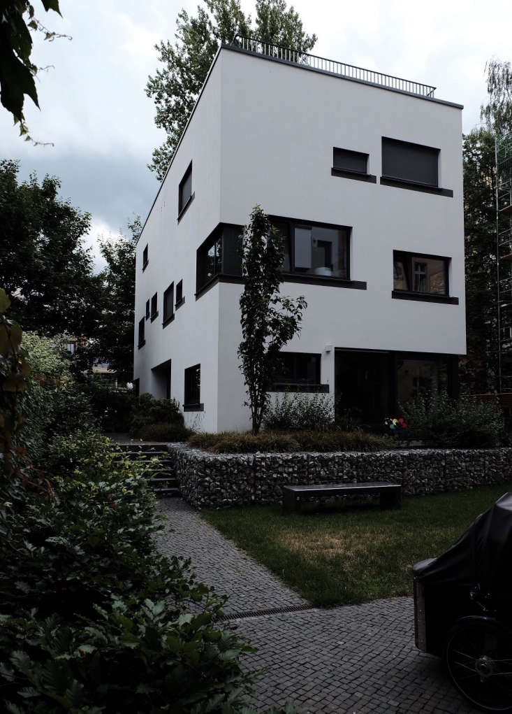 The cube-shaped, lintel-patternedhouse is set in a green courtyard and has a roof terrace.