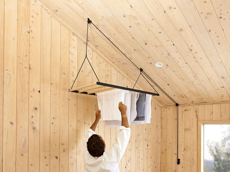 Object of Desire A Hanging Laundry Rack from a New Zealand Maker Made of steel, wood, and braided yachting rope, the drying rack hangs from the ceiling and raises and lowers for easy access. A steel cleat, affixed to the wall, tethers extra rope.