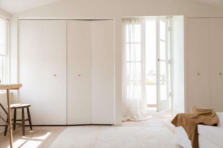Folding closet doors are updated with wood cube pulls; gauze curtains soften the room.