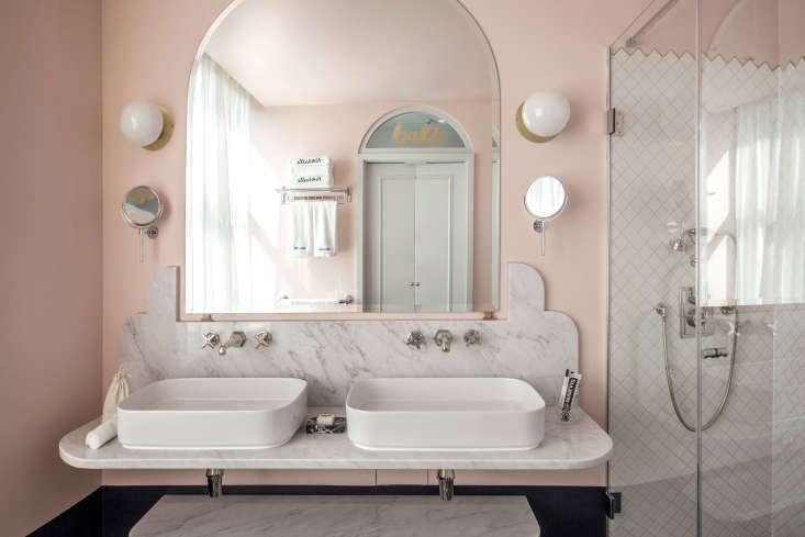 Scalloped Carrara marble and sawtooth-edged tiles against shell pink walls in a fanciful—and spacious—bath.